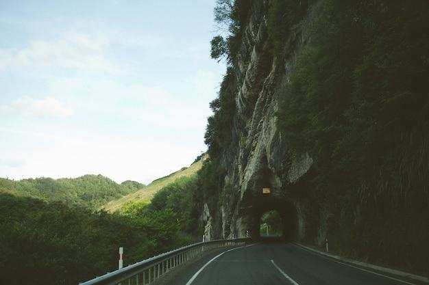 Vista fascinante da estrada através do arco de penhasco rochoso cercado por árvores e montanhas Foto gratuita