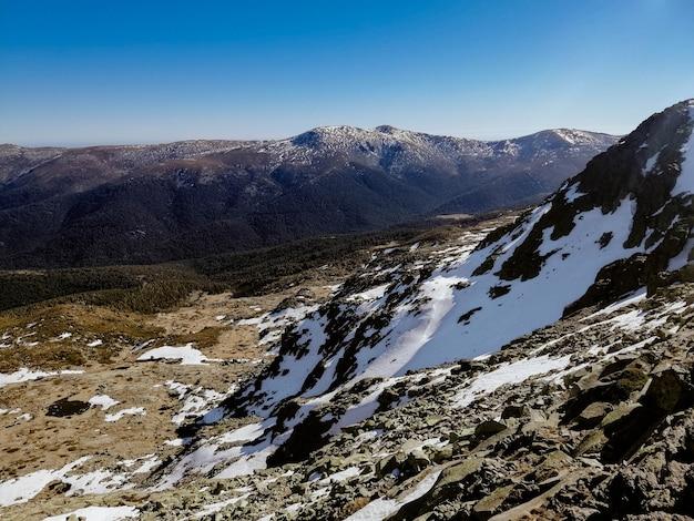 Vista fascinante da montanha penalara, na espanha, coberta de neve em um dia ensolarado Foto gratuita