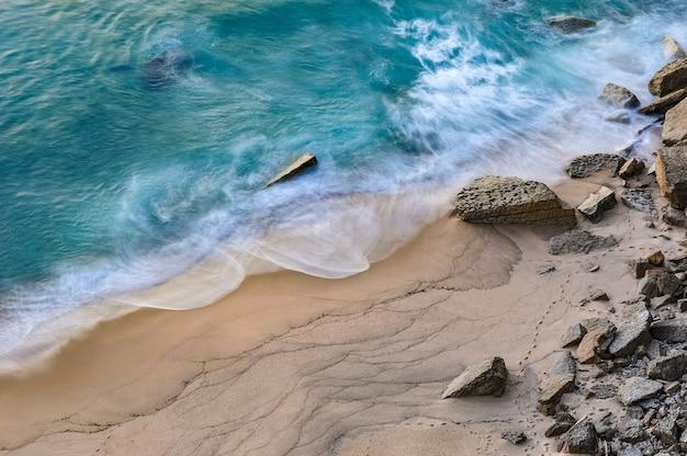 Vista fascinante das ondas do oceano batendo na praia Foto gratuita