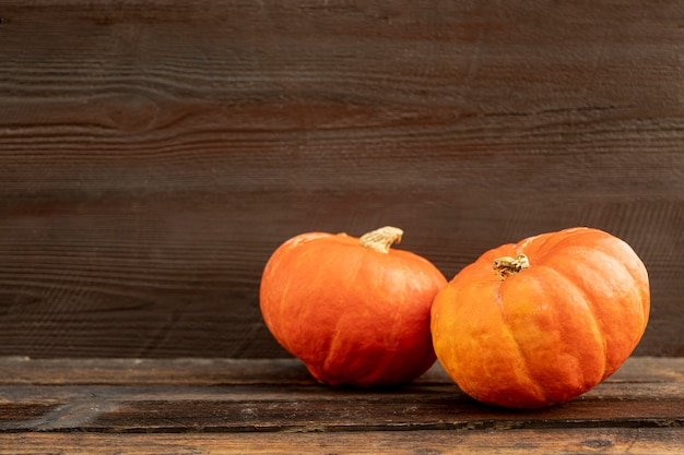Vista frontal abóboras laranja na mesa de madeira Foto gratuita
