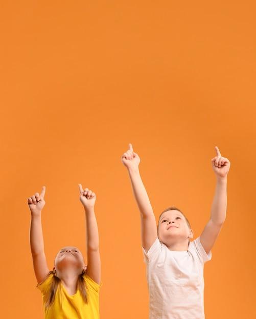 Vista frontal adoráveis crianças apontando para cima Foto gratuita