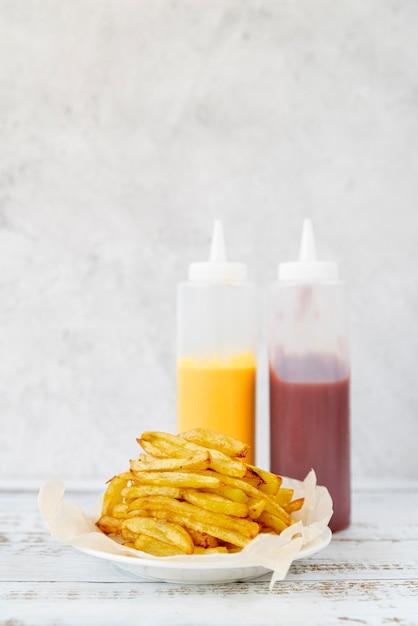 Vista frontal batatas fritas na mesa de madeira Foto gratuita