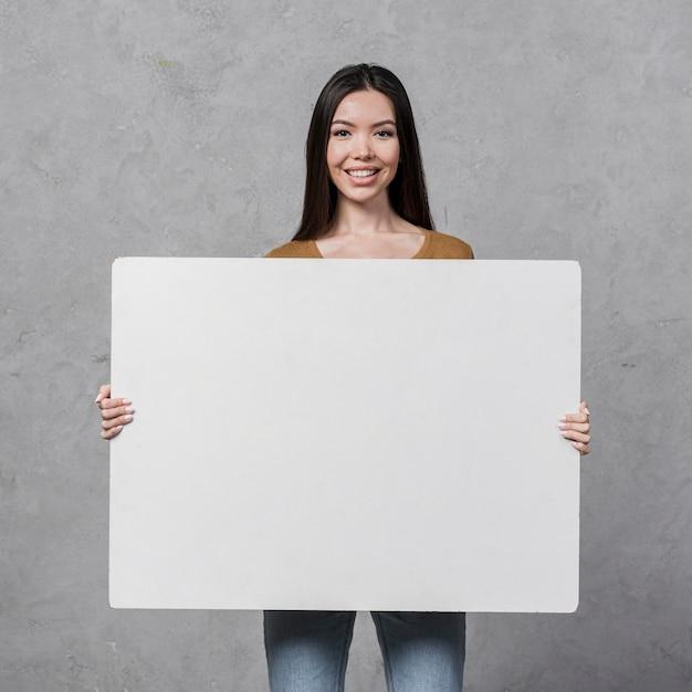 Vista frontal bela jovem segurando um cartaz Foto gratuita