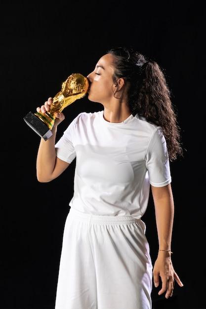 Vista frontal cabe mulher beijando troféu Foto gratuita