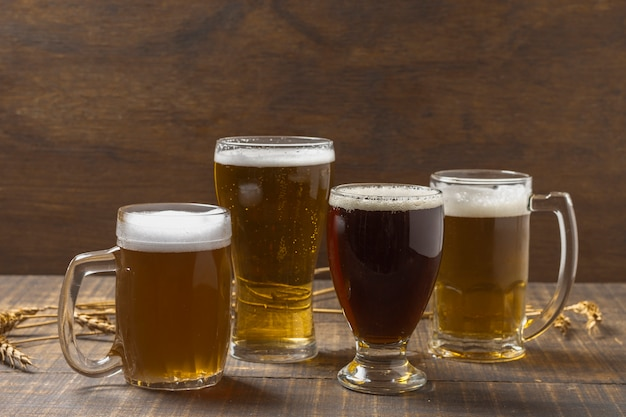 Vista frontal caneca e copos com cerveja na mesa Foto gratuita