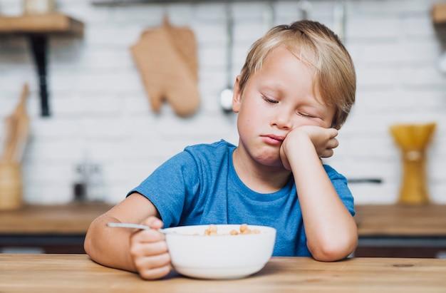 Vista frontal cansado garoto tentando comer seus cereais Foto gratuita
