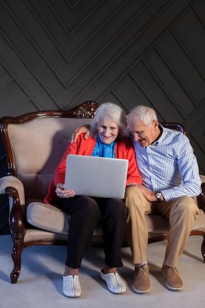 Vista frontal casal de idosos usando um laptop Foto gratuita