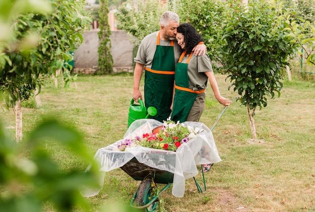 Vista frontal casal feliz com carrinho de mão Foto gratuita