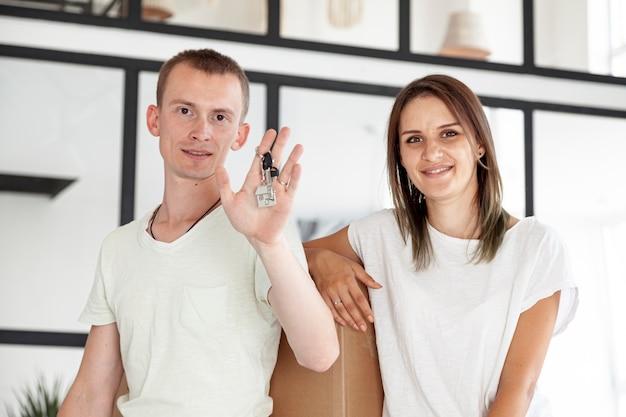Vista frontal casal segurando uma chave para sua nova casa Foto gratuita