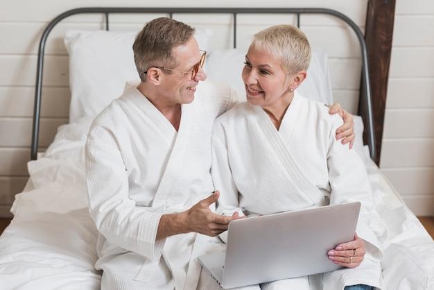 Vista frontal casal sênior olhando juntos em um laptop na cama Foto gratuita
