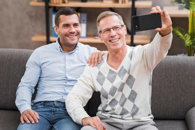 Vista frontal com pai e filho tomando uma selfie Foto gratuita