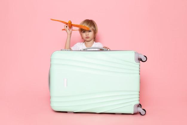 Vista frontal, criança menino, loiro, cabelos, tocando, com, avião laranja brinquedo, ligado, a, cor-de-rosa, escrivaninha Foto gratuita