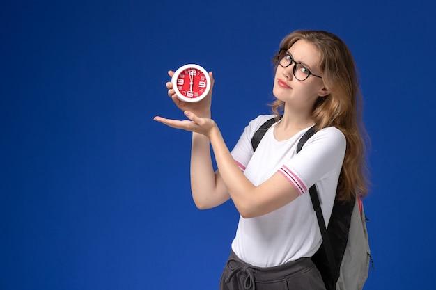 Vista frontal da aluna em camisa branca com mochila segurando relógios na parede azul Foto gratuita