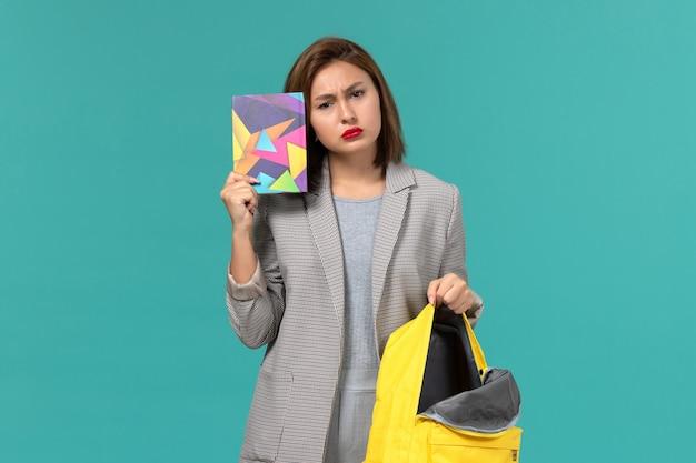 Vista frontal da aluna em jaqueta cinza segurando uma mochila amarela e um caderno na parede azul clara Foto gratuita