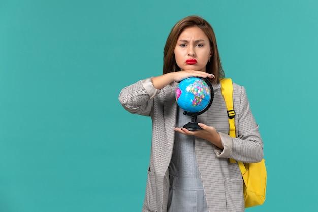 Vista frontal da aluna em uma jaqueta cinza com sua mochila amarela segurando o globo na parede azul clara Foto gratuita