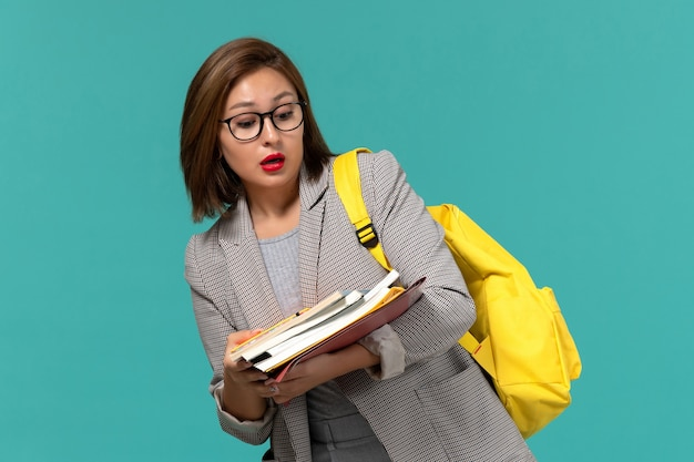 Vista frontal da aluna na mochila de jaqueta cinza amarela segurando livros na parede azul Foto gratuita