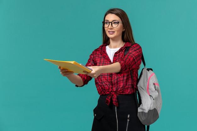 Vista frontal da aluna usando mochila e segurando arquivos na parede azul clara Foto gratuita