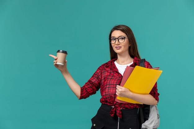 Vista frontal da aluna usando mochila segurando arquivos e café na parede azul Foto gratuita