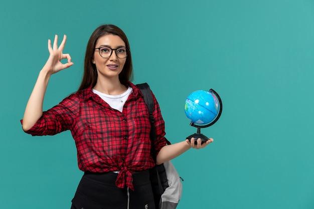 Vista frontal da aluna usando mochila segurando o globo na parede azul clara Foto gratuita