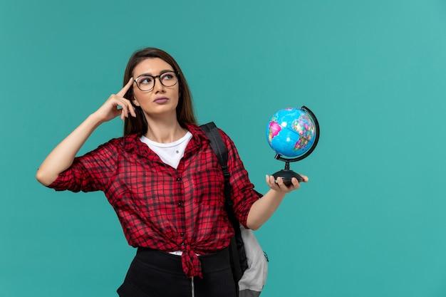 Vista frontal da aluna usando mochila segurando o pequeno globo pensando na parede azul clara Foto gratuita