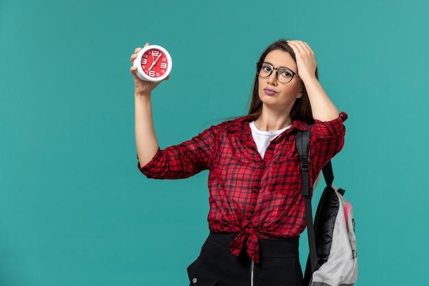 Vista frontal da aluna usando mochila segurando relógios na parede azul Foto gratuita