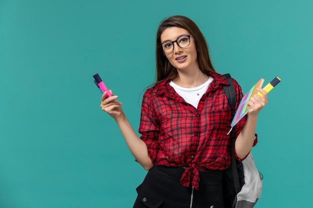 Vista frontal da aluna usando uma mochila segurando um caderno e canetas hidrográficas na parede azul Foto gratuita