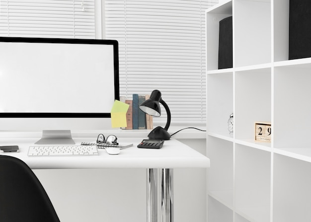 Vista frontal da área de trabalho com tela de computador e lâmpada Foto gratuita