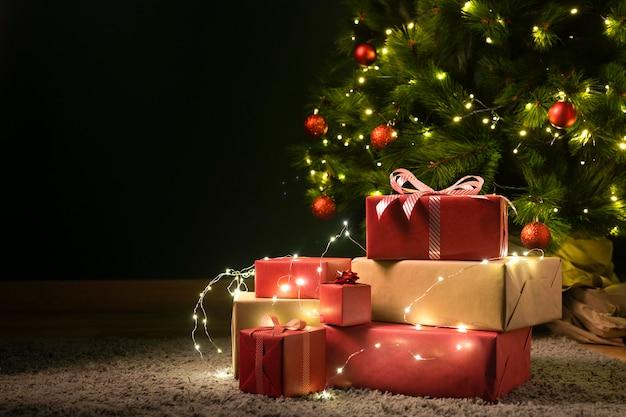 Vista frontal da árvore de natal e presentes Foto Premium