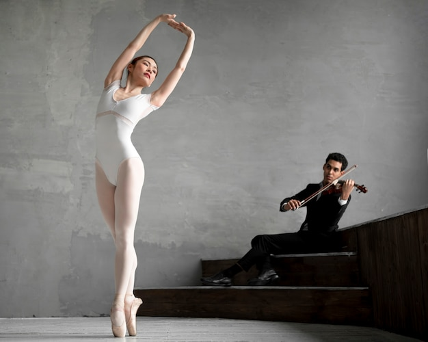 Vista frontal da bailarina dançando a música tocada pelo violinista masculino Foto gratuita