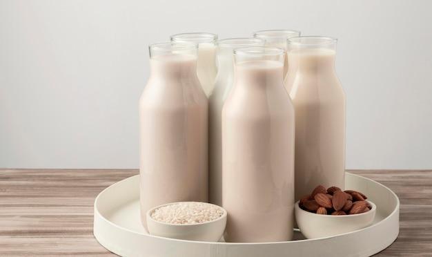 Vista frontal da bandeja com diferentes tipos de garrafas de leite Foto gratuita