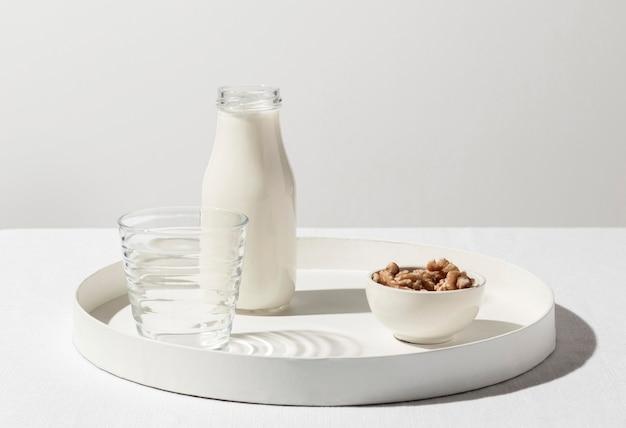 Vista frontal da bandeja com garrafa de leite e nozes Foto gratuita