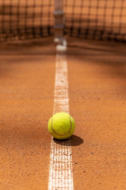 Vista frontal da bola de tênis no campo do tribunal Foto gratuita