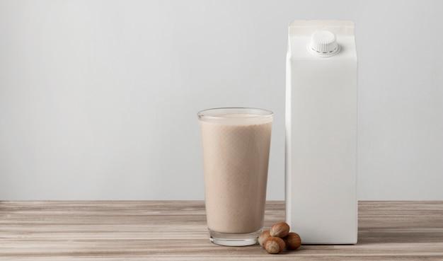 Vista frontal da caixa de leite com vidro e nozes Foto gratuita