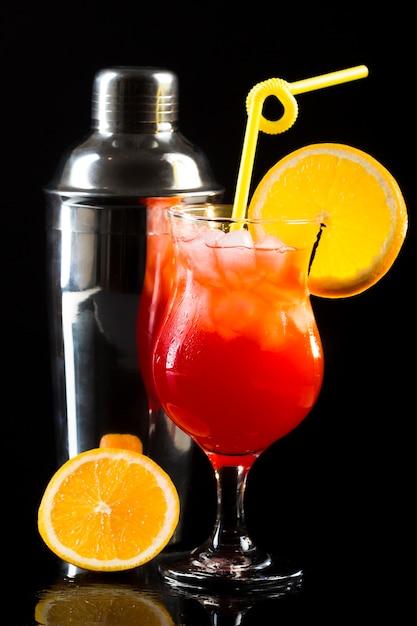 Vista frontal da coqueteleira e copo com laranja e palha Foto gratuita