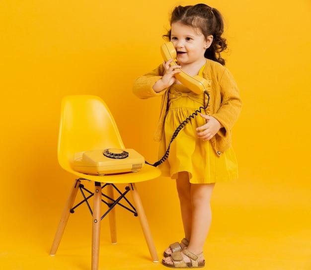 Vista frontal da criança adorável posando enquanto segura o telefone Foto gratuita