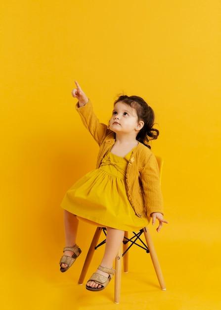 Vista frontal da criança posando enquanto está sentado na cadeira e apontando para cima Foto gratuita