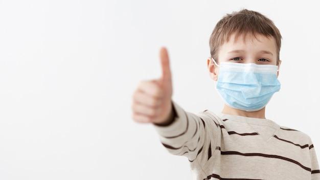 Vista frontal da criança vestindo máscara médica desistindo polegares Foto gratuita