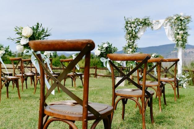 Vista frontal da decoração floral de eustomas brancos e ruscus de cadeiras chiavari marrons ao ar livre e arco cerimonial de casamento Foto gratuita