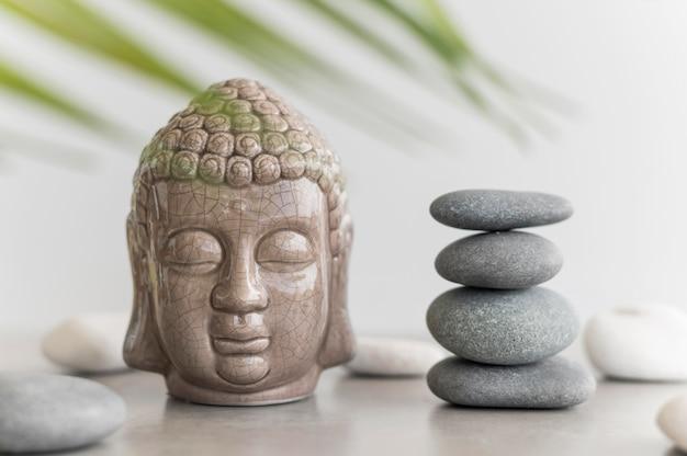 Vista frontal da estátua da cabeça de buda com pedras Foto Premium