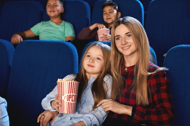 Vista frontal da família passando algum tempo juntos no cinema. atraente jovem mãe e filha se abraçando e sorrindo enquanto assistem um filme e comem pipoca Foto gratuita