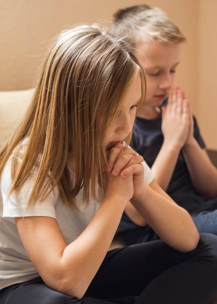 Vista frontal da família rezando Foto gratuita