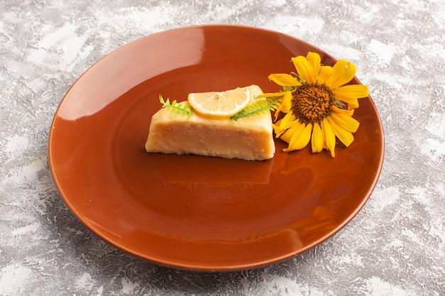 Vista frontal da fatia de bolo delicioso com limão dentro da placa marrom com girassol na superfície da luz Foto gratuita