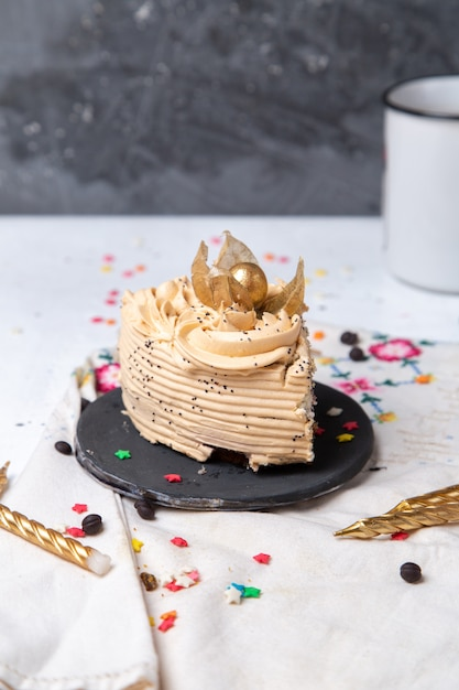 Vista frontal da fatia de bolo delicioso dentro do prato escuro com velas e estrelinhas na mesa de luz Foto gratuita