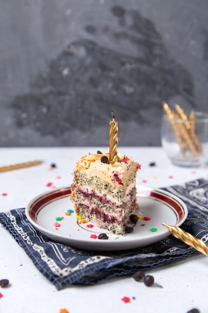 Vista frontal da fatia de bolo dentro da placa com vela acesa Foto gratuita