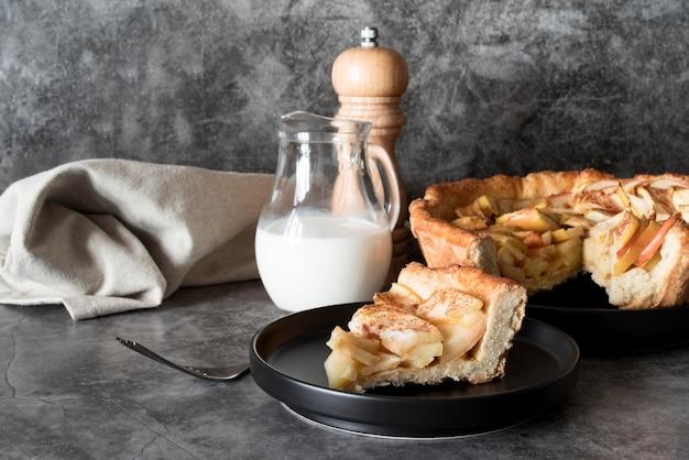Vista frontal da fatia de torta de maçã no prato com leite Foto gratuita