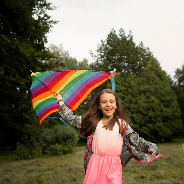 Vista frontal da garota feliz se divertindo com uma pipa Foto gratuita