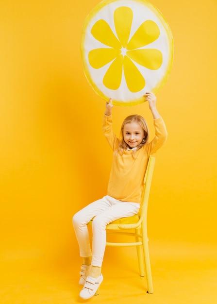 Vista frontal da garota posando enquanto segura a decoração de fatia de limão Foto gratuita