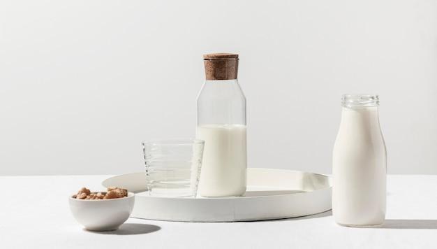 Vista frontal da garrafa de leite com nozes na bandeja Foto gratuita