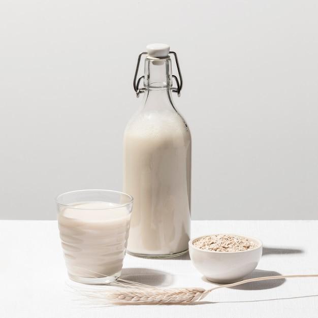 Vista frontal da garrafa de leite com vidro e aveia Foto gratuita