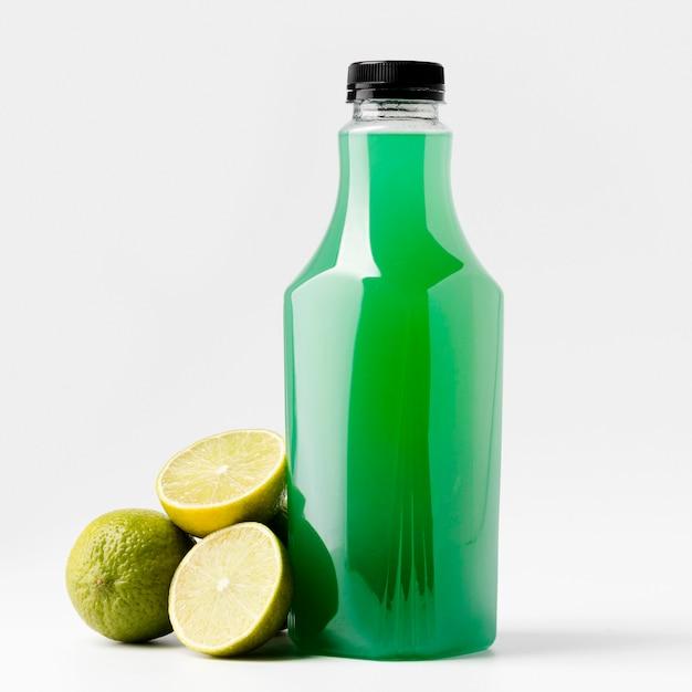 Vista frontal da garrafa de suco verde com frutas de limão Foto gratuita